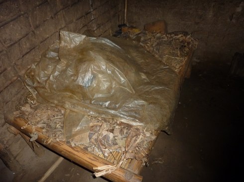 Bed with straw mattress and plastic blanket