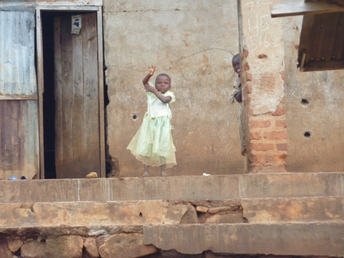 A girl waving at us (being muzungu) while we drive through Nyankunde, but notice the bullet holes